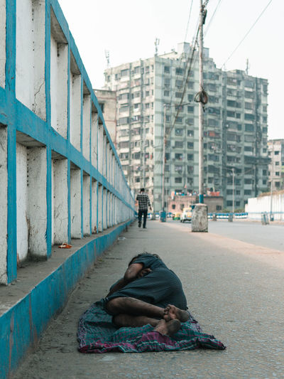 Man sleeping on street against buildings in city