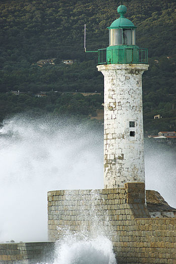 Lighthouse by sea against building