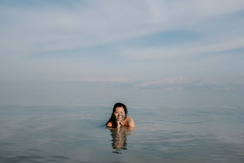 Portrait of young woman swimming in sea against cloudy sky