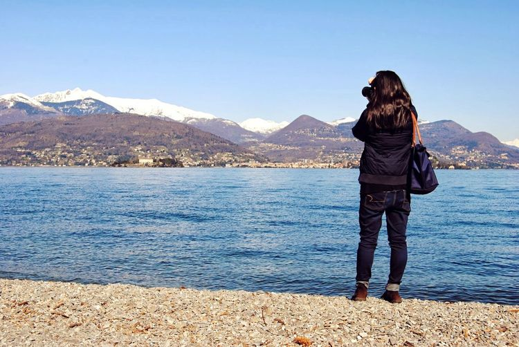 Full Length Rear View Of Woman Photographing River And Mountains