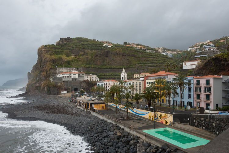 View of Ponta do Sol village in Madeira Architecture City Cityscape Madeira Nature Panorama Panoramic Portugal Portuguese Travel Aerial View Architecture Beach Buildings City Island Landscape Mountain Outdoors Ponta Do Sol Sea Seascape Village Water Waves