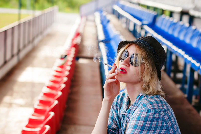 Woman smoking cigarette in stadium