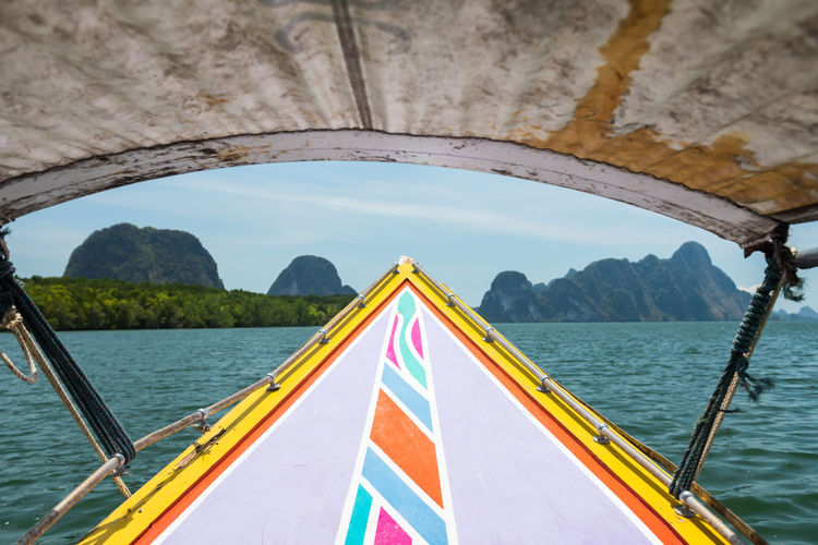 Longtail wooden boat sail on ocean in phang nga bay with green island and mangrove forest, thailand.