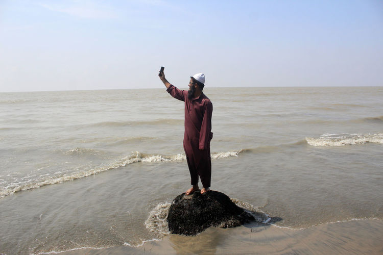 Man taking selfie while standing on rock at beach