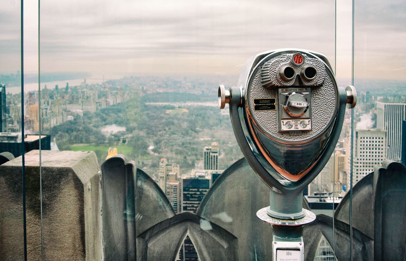 Close-up of coin-operated binoculars against buildings in city