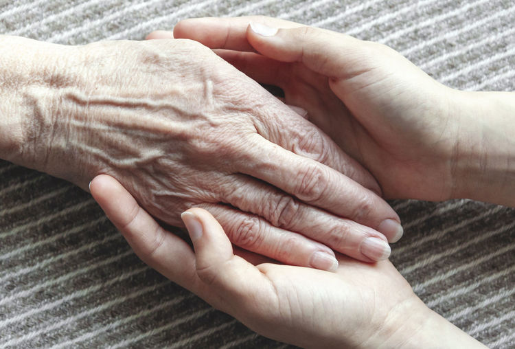 Young hands holding old wrinkled hand