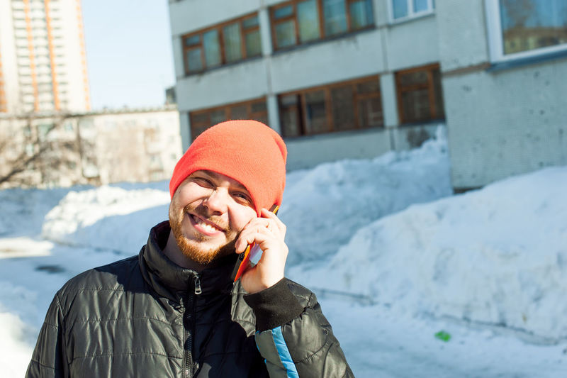 Portrait Of Man In Warm Clothing Talking On Mobile Phone Against Building
