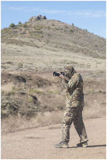 Side view of army soldier photographing with camera on field