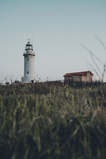 Lighthouse on field by building against sky