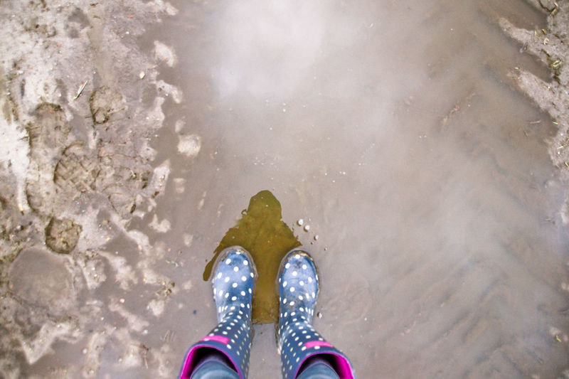 Low section of woman wearing ankle boots while standing at beach