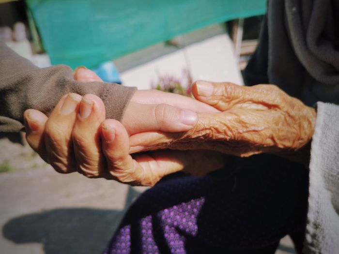 Midsection of senior woman holding grandchild hand outdoors