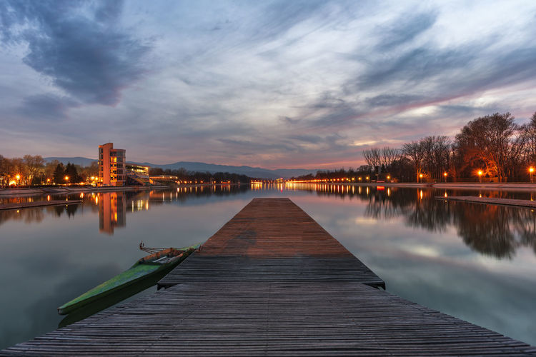 Sunset over rowing channel in Plovdiv city - european capital of culture 2019, Bulgaria, Europe. Pier with boat in front. Architecture Reflection Illuminated Lake Sunset Nature Water Plovdiv Bulgaria Rowing Kayak Kayaking Sport Boat Pier Wooden Channel Urban Skyline Cityscape Sky Evening Lights City