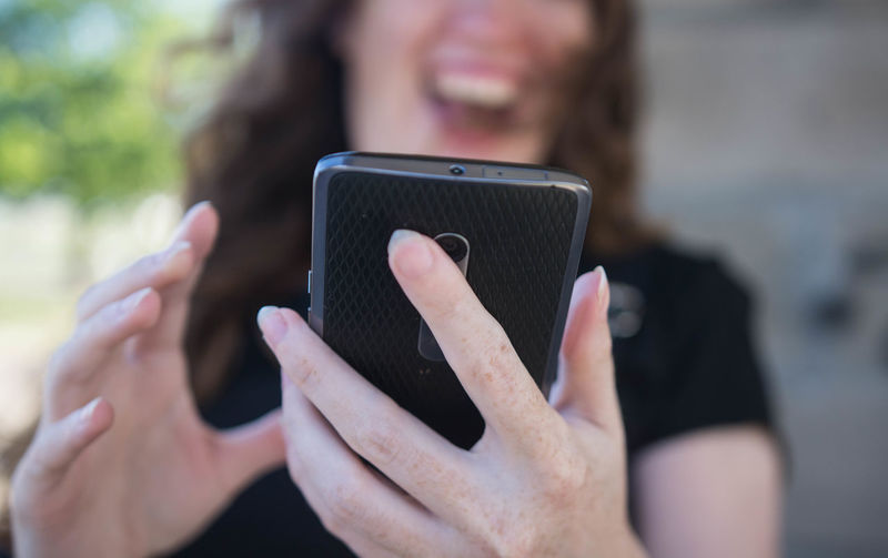 Young woman using a smartphone outdoors and laughing at what she sees on the screen Smart Phone Wireless Technology Communication Mobile Phone Portable Information Device Technology Real People One Person Holding Connection Focus On Foreground Lifestyles Using Phone Telephone Leisure Activity Adult Women Human Hand Outdoors Hand Woman Portrait Candid Spontaneous Laughing Happy Laugh Meme