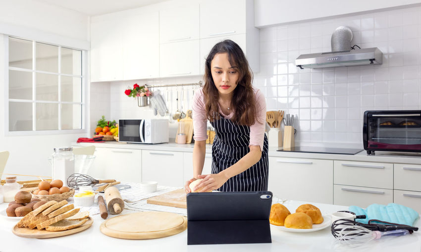 Young woman holding food while standing at home