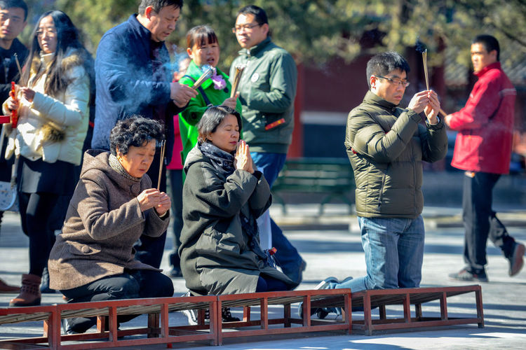 Worshippers hold incense sticks and pray at Yonghegong Lama Temple in Beijing, China. ASIA Beijing Lama Temple Monastery Smoke Worshippers Adult Boys Budhism Casual Clothing China Day Digital Camera Group Group Of People History Lama Leisure Activity Lifestyles Looking Males  Medium Group Of People Men Outdoors People Prayer Real People Religion Sitting Standing Stick Temple Warm Clothing Winter Women Yonghe Yonghegong