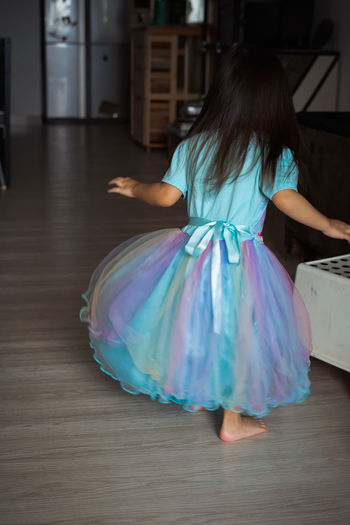 Toddler spinning around while wearing her rainbow dress at home.