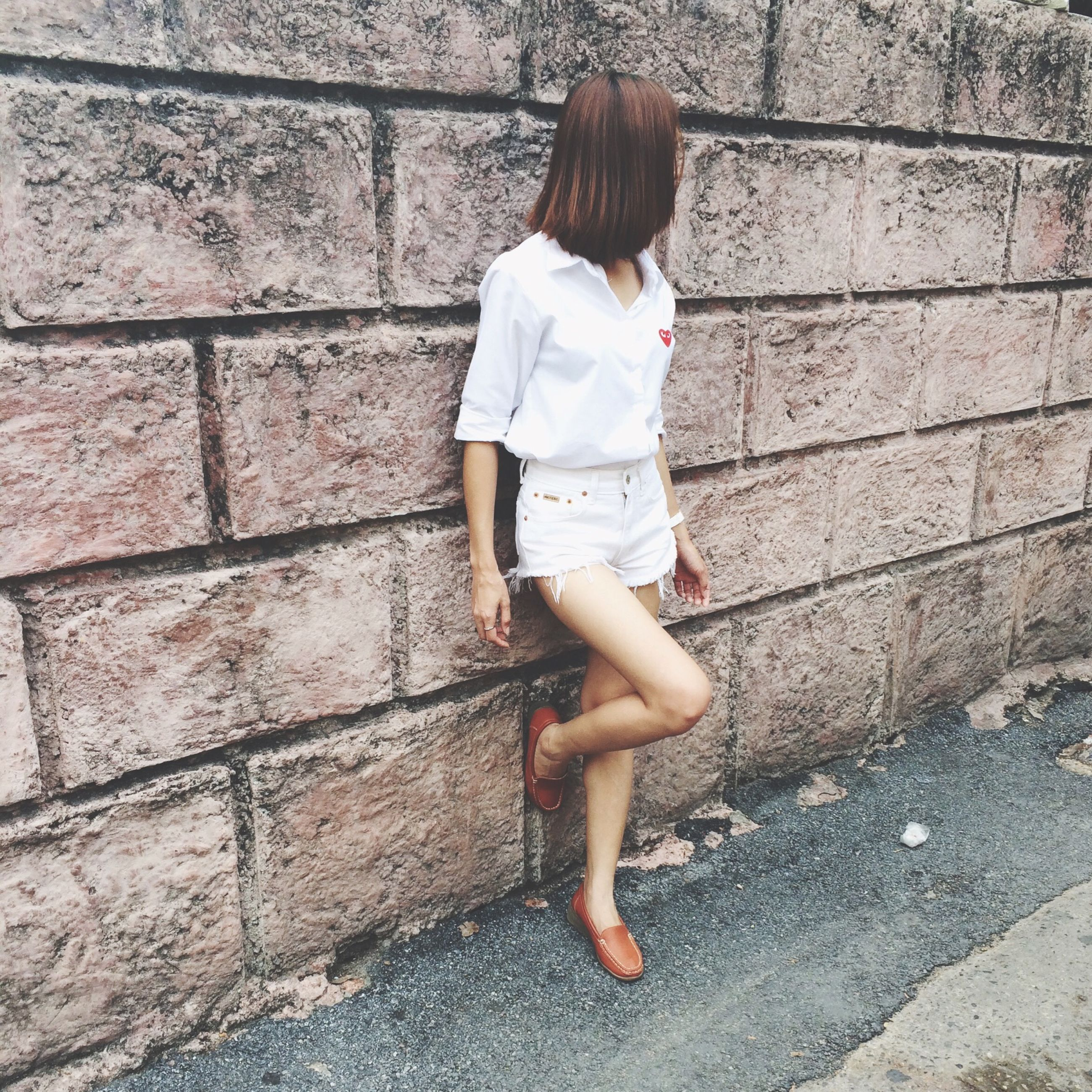 lifestyles, casual clothing, full length, standing, leisure activity, brick wall, wall - building feature, walking, rear view, childhood, day, person, front view, sidewalk, outdoors, side view, built structure