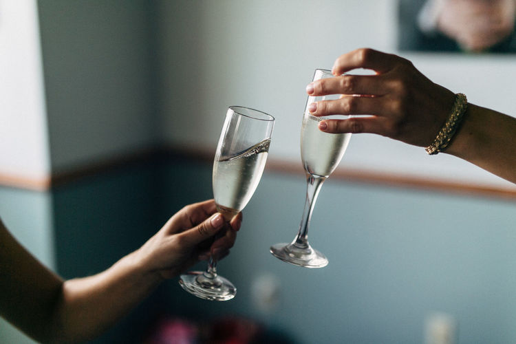 Cropped hands of friends toasting champagne flutes against wall
