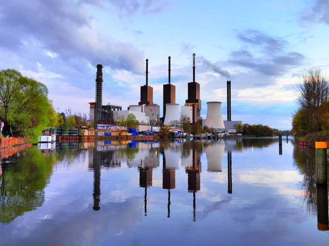 combined heat and power plant is reflecting in water Canal Chimney Cooler Cooling Tower Heat Plant Heating Plant Heating Station Industry Power House Power Plant Power Station Powerhouse Reflection Reflections Reflections In The Water Sky Sky And Clouds Smoke Smoke Pipe Smoke Stack Smokestack Stack Water Waterfront Windy Day