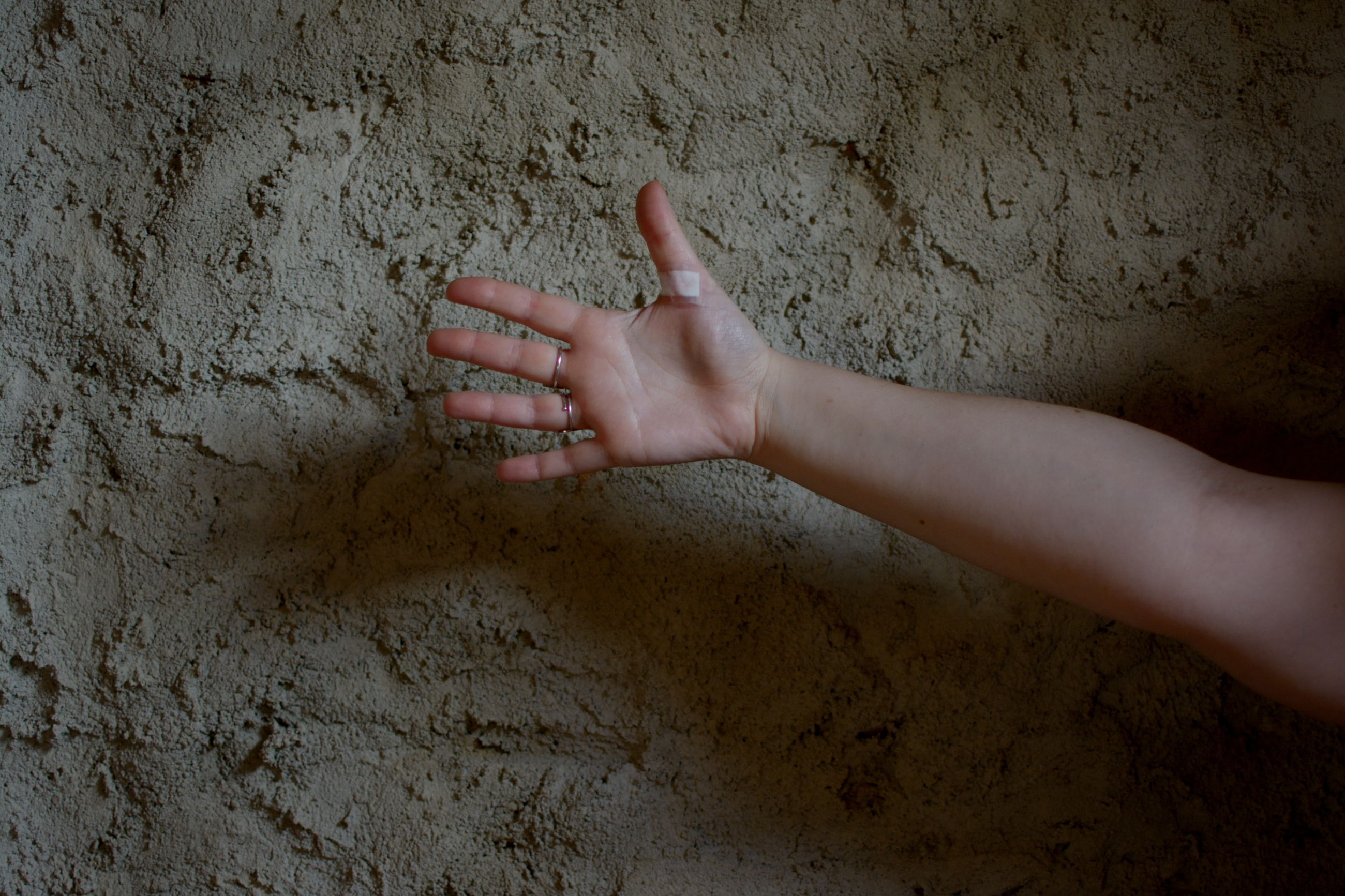 MIDSECTION OF PERSON TOUCHING WALL WITH HAND