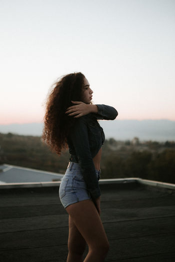Young woman posing while standing outdoors during sunset