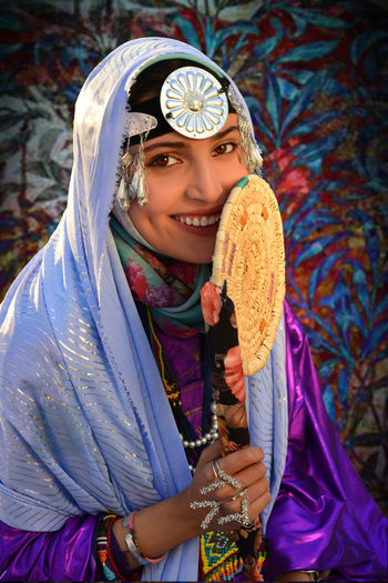 Portrait of happy young woman in traditional clothing holding hand fan