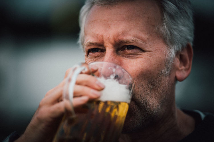 Close-up of mature man drinking beer