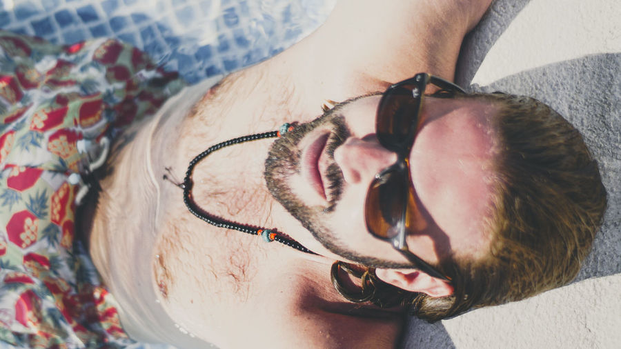 Portrait of shirtless wearing sunglasses at beach