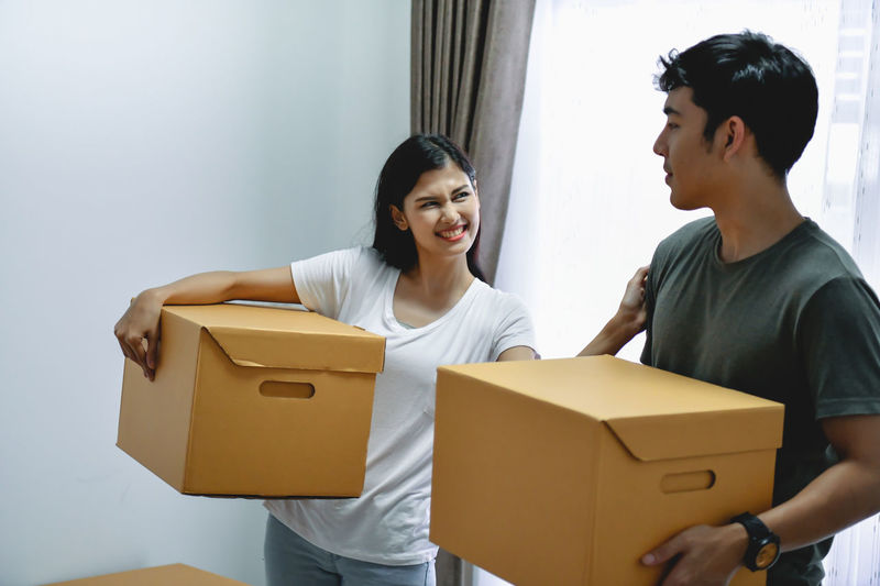 Adult Box Box - Container Cardboard Cardboard Box Carrying Casual Clothing Couple - Relationship Front View Holding Indoors  Real People Smiling Standing Three Quarter Length Togetherness Two People Women Young Adult Young Men Young Women