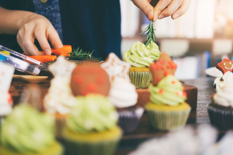 Midsection of person garnishing cup cakes on table