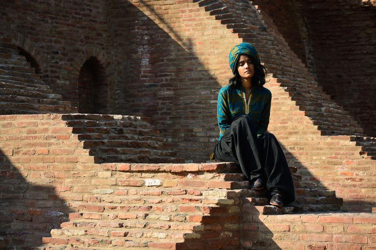 Woman sitting on brick steps