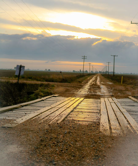 Dirt road against sky during sunset