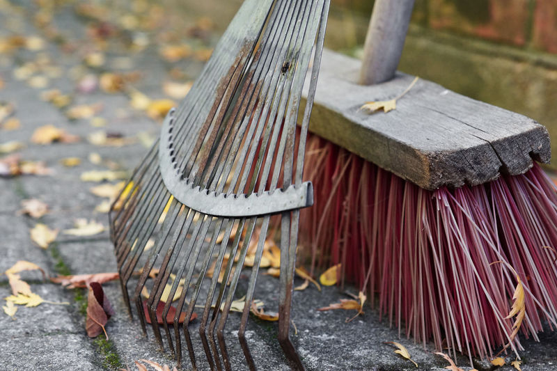 Close-Up Of Broom With Rake On Footpath During Autumn