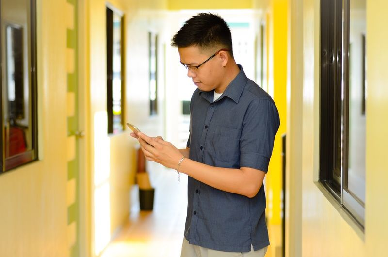 Young Man Using Mobile Phone Away While Standing In Corridor