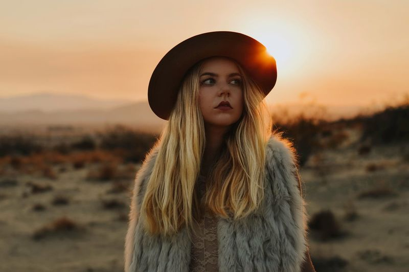 Portrait of woman wearing hat standing against sun during sunset