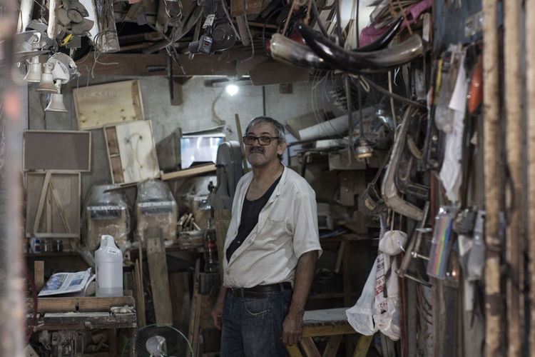 Portrait of mature man standing in messy workshop