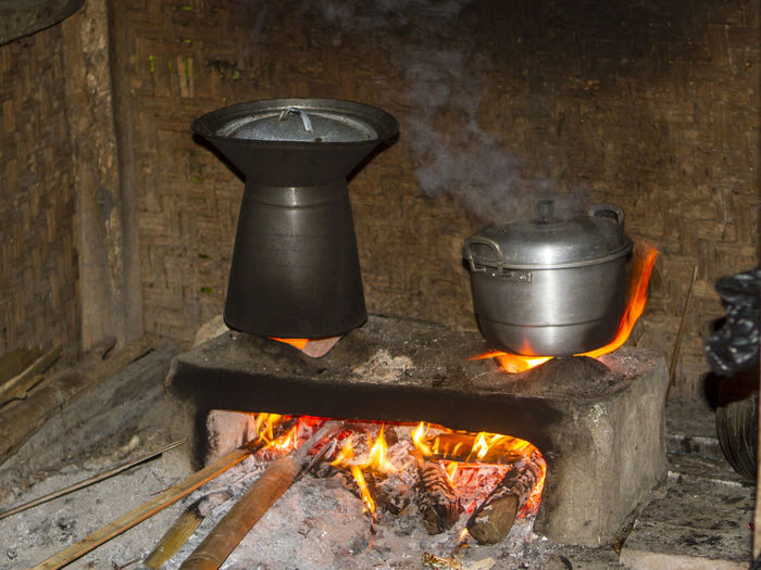 Cooking utensils on wood burning stove in traditional kitchen