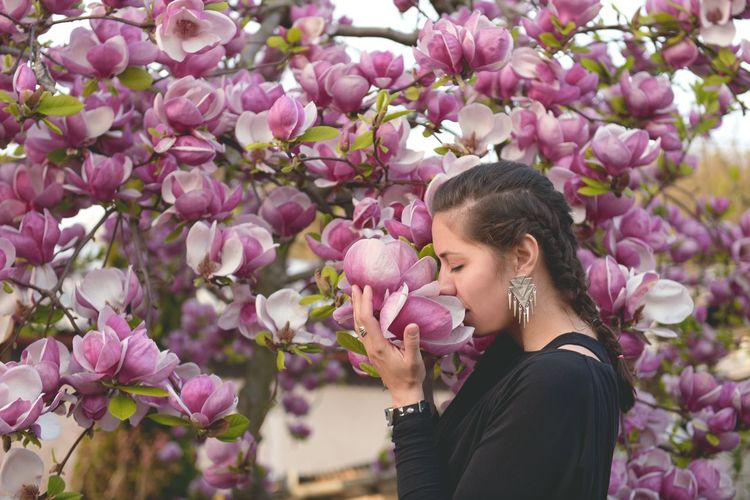 Young Woman Smelling Pink Flowers Blooming During Springtime
