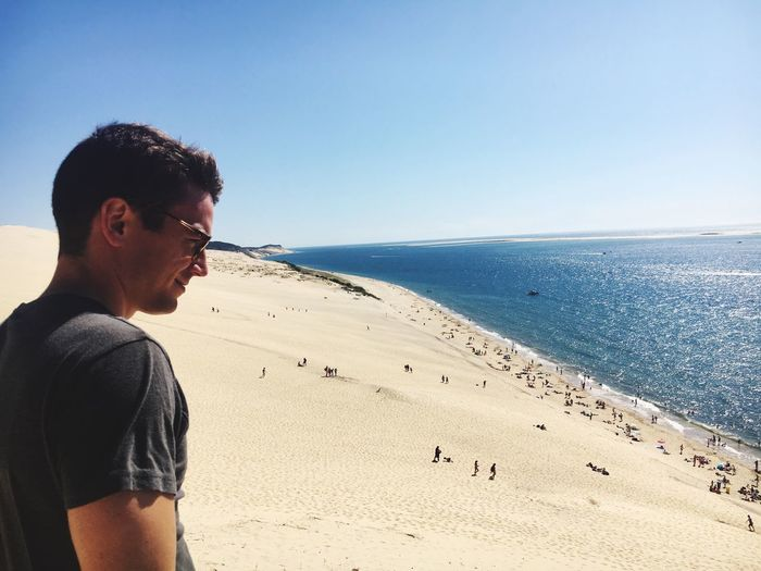 Man on beach by sea against sky