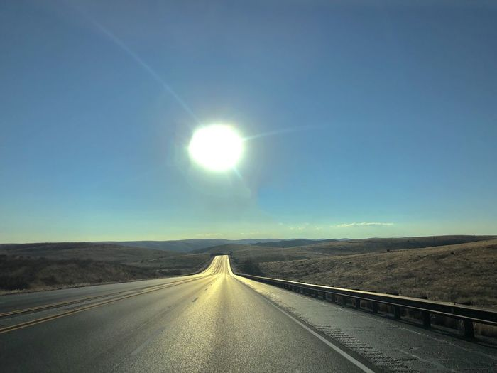 Open highway in New Mexico. New Mexico Bright Dividing Line Lens Flare Outdoors Day Non-urban Scene Diminishing Perspective Beauty In Nature No People Landscape Empty Road Highway Absence Desert Landscape The Way Forward Copy Space Blue Sky Sun vanishing point Road Countryside Sun Reflection Sun Flare Roadtrip Capture Tomorrow