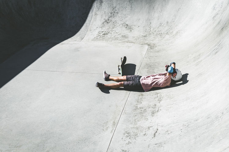 High angle view of man sitting on concrete wall