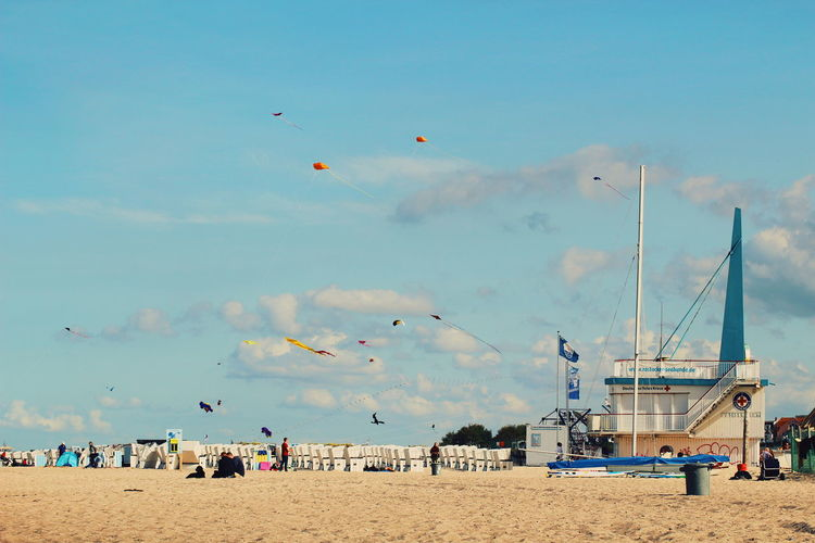 People enjoying at beach against blue sky