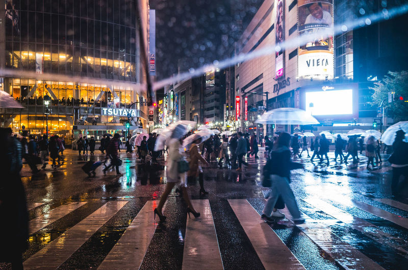 Crowd Walking On Street During Rainy Season In City At Night