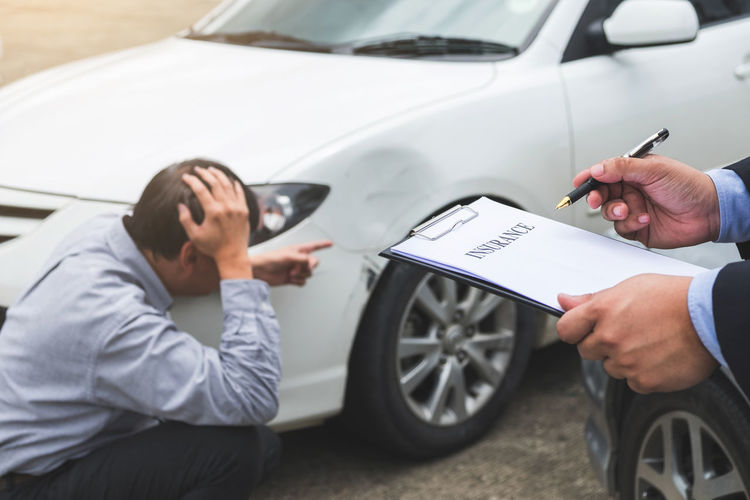 Cropped Image Of Insurance Agent With Document By Owner Showing Damaged Car