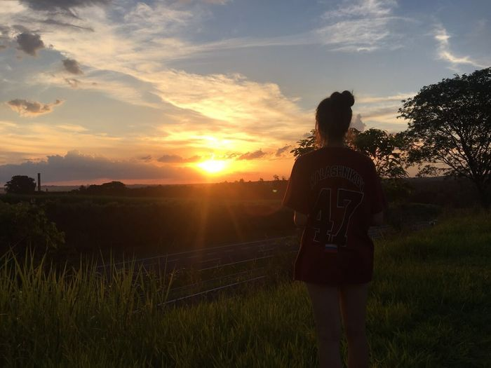 Sunset Nature Sky Field Grass Rear View Real People Lifestyles Scenics Outdoors Tranquility Sun Beauty In Nature Standing Growth Landscape One Person Women Cloud - Sky Tree