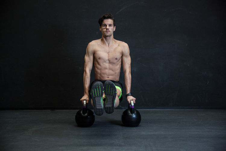 Portrait Of Shirtless Man Exercising With Kettlebells In Gym