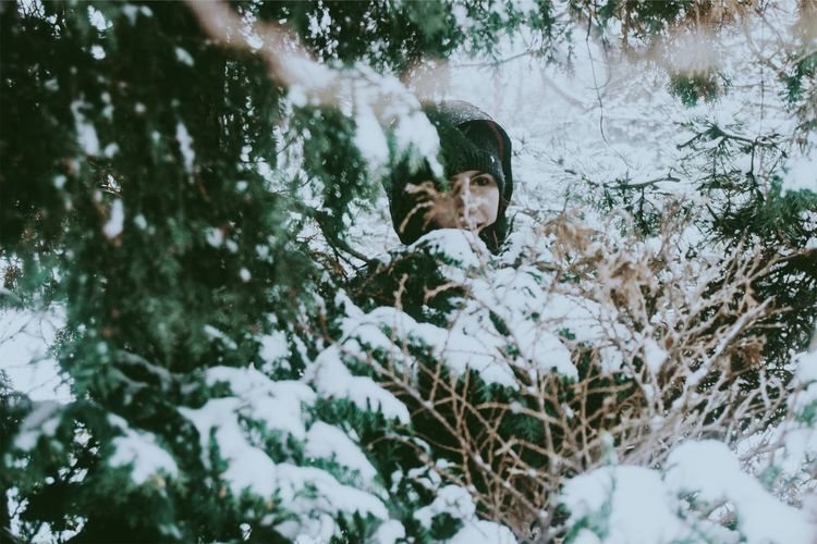 Woman Amidst Snow Covered Tree In Forest