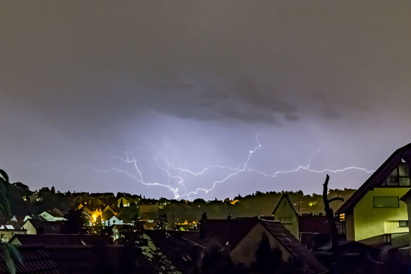 Panoramic view of lightning over houses against sky