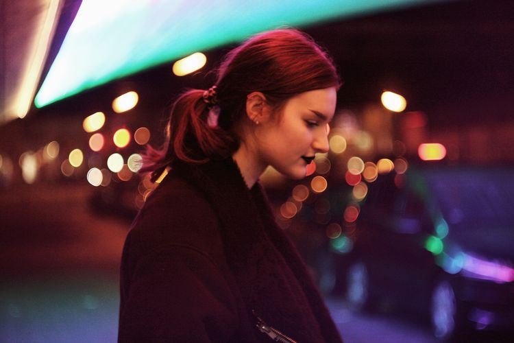 Close-up of young woman standing in illuminated street