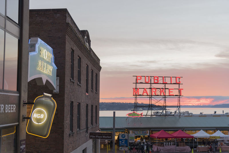 Pikes Place Market at sunset on the Seattle waterfront with neon Public market sign. Economy Elliott Bay Pink Post Alley Puget Sound Red Seattle Sign Tourists Travel View Washington Destination District Glowing Landmark Neon Pikes Place Market Public Market Shop Sky Sunset Tourism Vibrant Adventures In The City